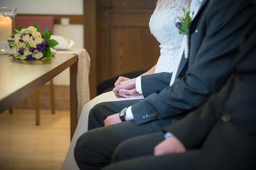 Hochzeitspaar hält sich die Hand bei der standesamtlichen Trauung