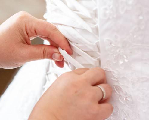 Schnüren des Brautkleids bei den Vorbereitungen während der Hochzeitsreprtage