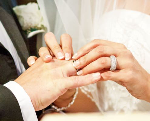 Ringtausch, Braut steckt ihrem Mann den Ehering an