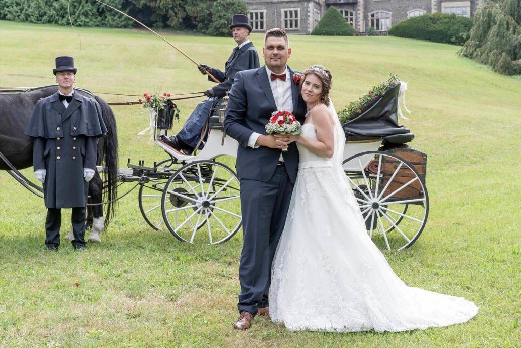 Brautpaar mit Hochzeitskutsche im Park vor dem Schloss Rauischholzhausen