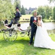 Hochzeitspaar vor der Hochzeitskutsche mit der Hochzeitsgesellschaft und Schloss im Hintergrund