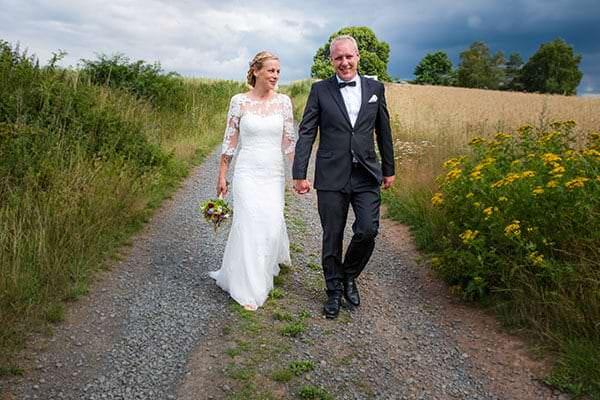 Hochzeitspaar auf einem Feldweg hand in hand. Der Himmel im Hintergrund wirkt bedrohlich dunkel.