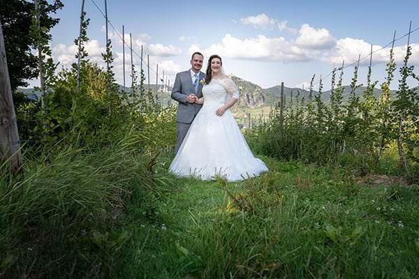 Hochzeitspaar bei ihrer Fotosession im Weinberg bei Bonn. Im Hintergrund ist der Drachenfelsen zu erkennen.