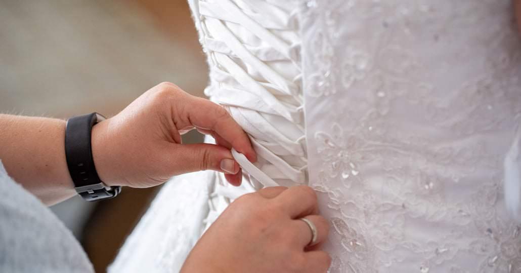 Vorbereitung der Braut beim schnüren des Hochzeitskleid