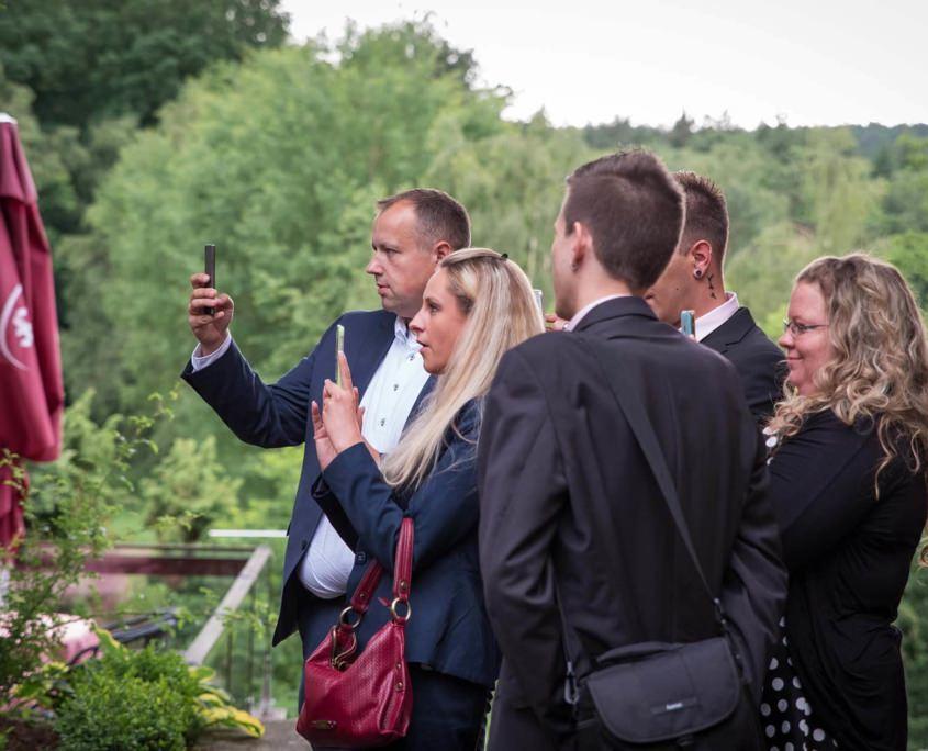 Gäste machen mit dem Handy Schnappschüsse bei einer Hochzeit