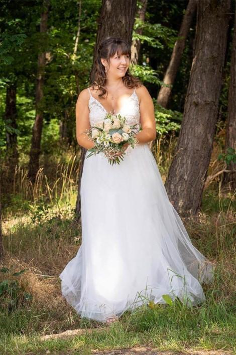 Braut unter den Bäumen in Kirchhain mit ihrem Hochzeitsstrauß.