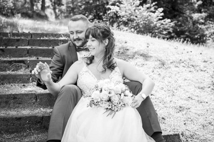 Brautpaar schaut sich ihre Eheringe gemeinsam an der Hand an.