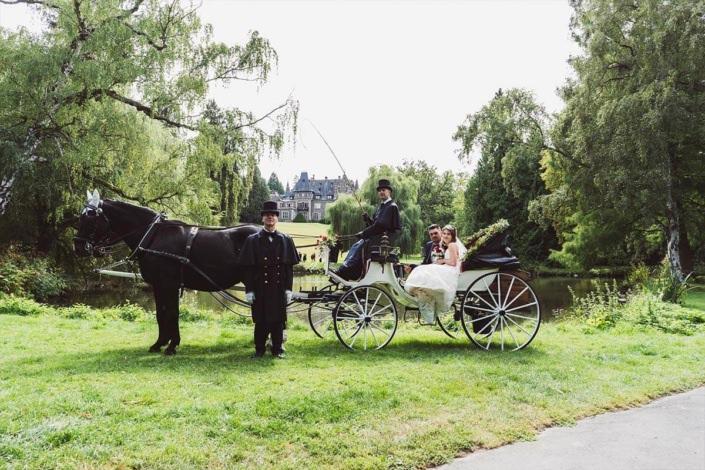 Brautpaar in Hochzeitskuttsche und Kutscher am Teisch im Schosspark mit dem Schloss von Rauischholzhausen im Hintergrund