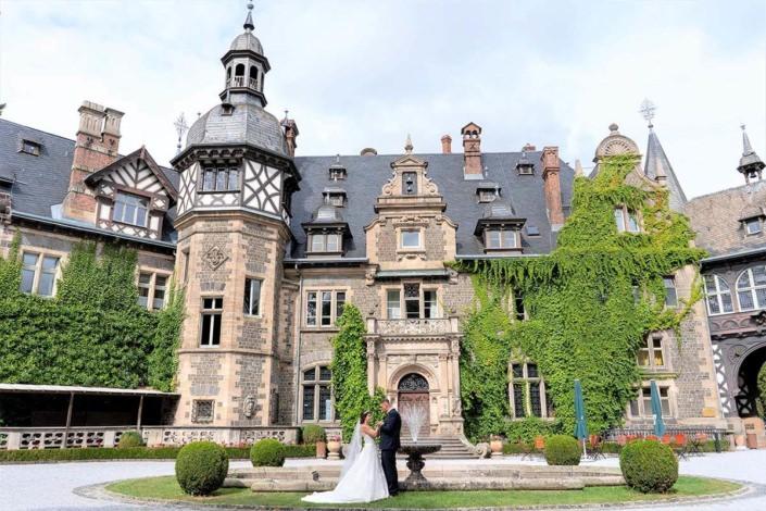 Hochzeitspaar am Springbrunnen vor dem Schloss in Rauischholzhausen
