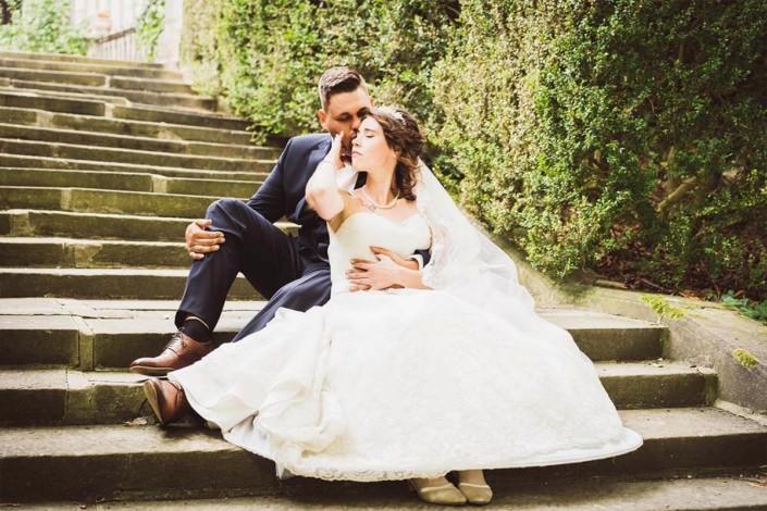 Hochzeitspaar sitzend auf einer Steintreppe vor dem Schloss in Rauischholzhausen