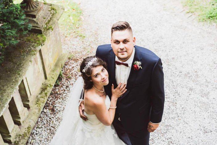 Brautpaar Arm in Arm mit direkten Blick in die Kamera in Rauischholzhausen im Schlosspark