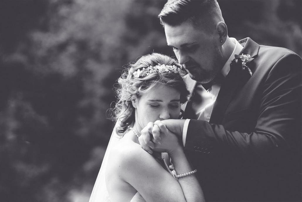 Braut gibt ihrem Mann einen Handkuss im Schlosspark von Rauischholzhausen