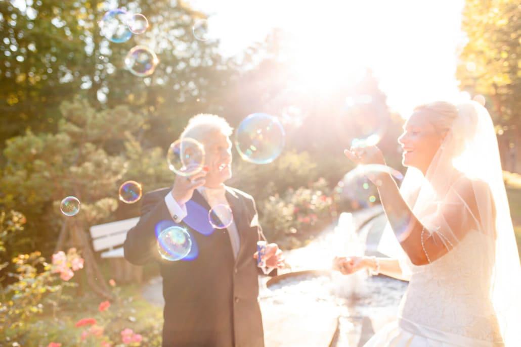 Hochzeitsfotograf mit Hochzeitspaar im Park beim Seifenblasen machen